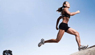 Benefits-of-hill-training picture with female athlete sprinting up hill